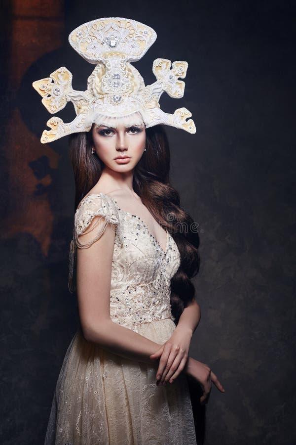 Art Woman avec une longue tresse dans une longue robe luxueuse et un casque fabuleux Reine de neige de fille posant sur un fond f photo libre de droits