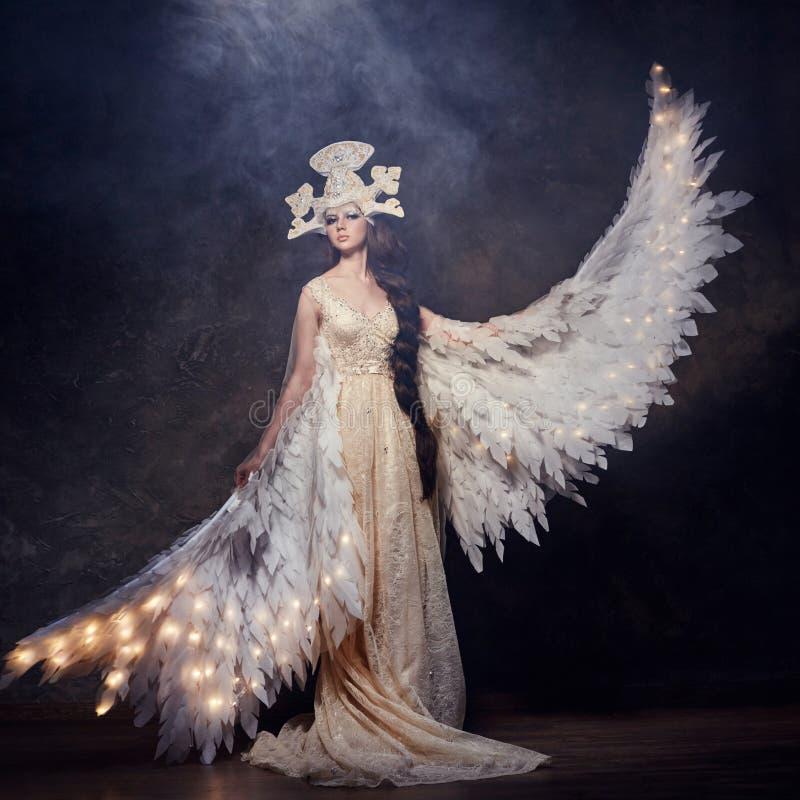 Art Woman-engel met vleugels in luxueuze lange kleding en fabelachtig hoofddeksel Meisjesvogel met lichtgevende vleugels die op d stock fotografie