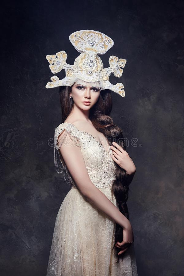 Art Woman with a long braid in a luxurious long dress and fabulous headpiece. Girl snow Queen posing on a dark background. Portrait of a woman fairy stock image
