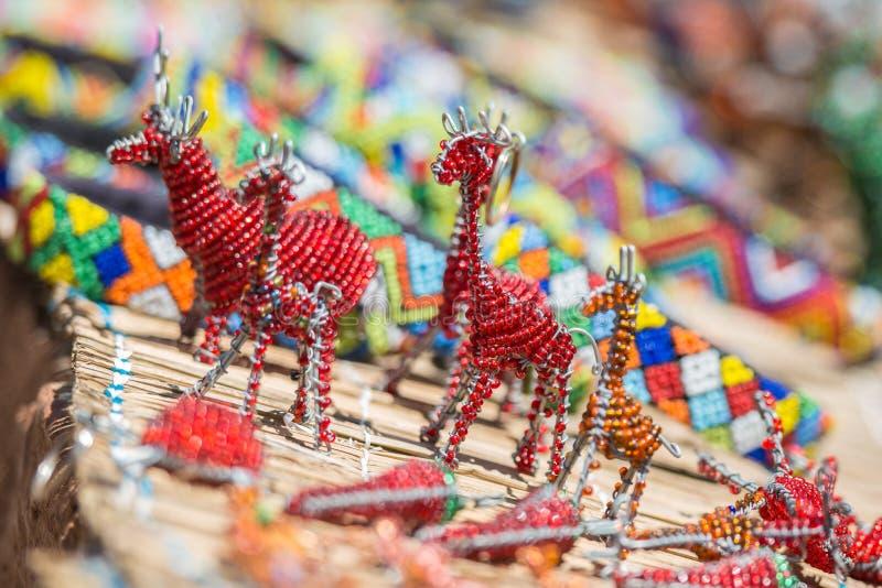 Arte africana brilhantemente colorida do grânulo dos girafas e dos outros animais com as esteiras frisadas roladas no fundo fotos de stock royalty free