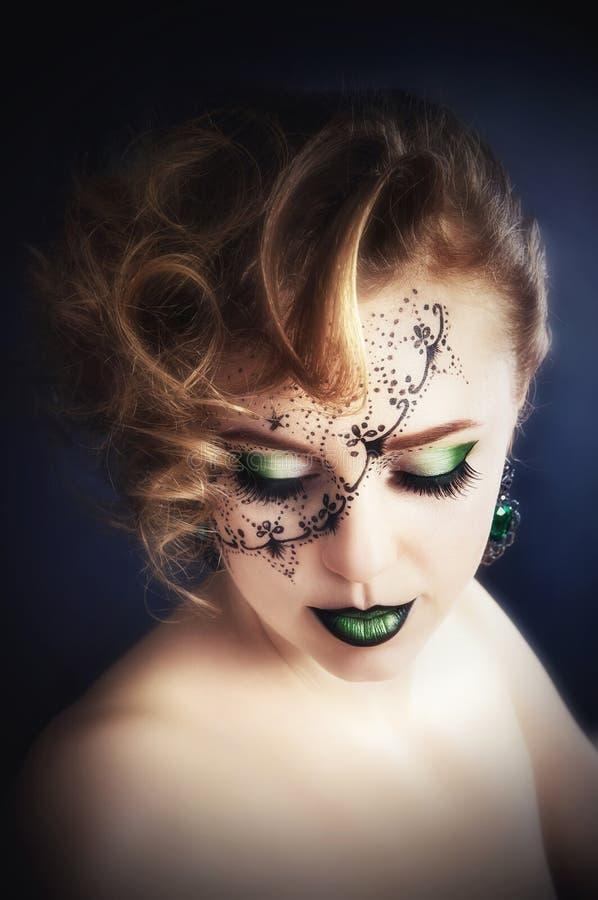 Arte, bella ragazza con un'immagine sul suo fronte immagini stock libere da diritti
