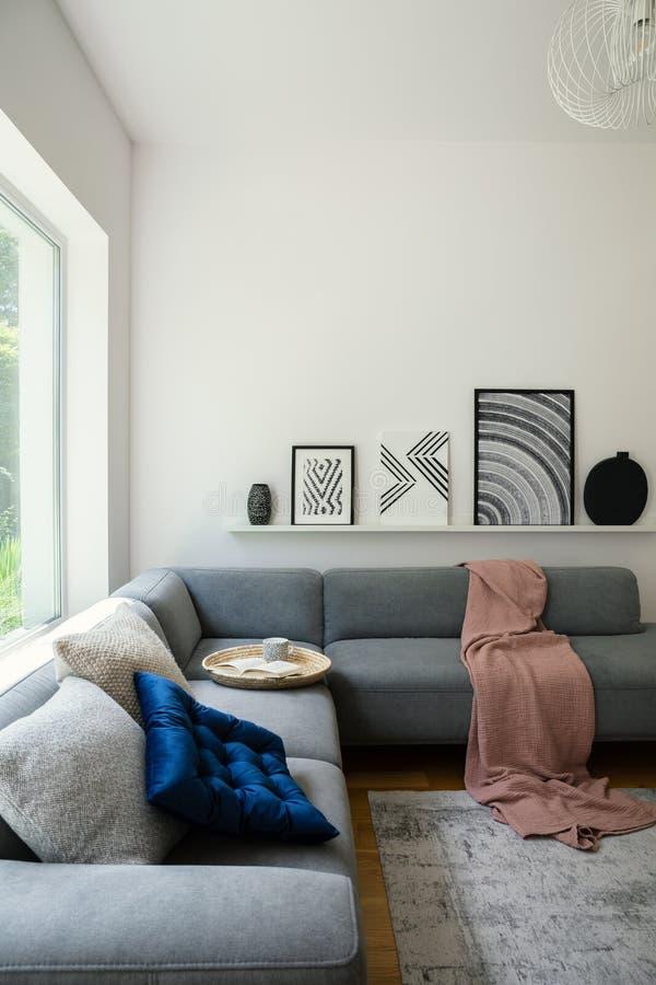 Arte blanco y negro y carteles en un estante sobre un sofá acogedor con un libro y una taza en una bandeja de mimbre en una relaj fotos de archivo libres de regalías