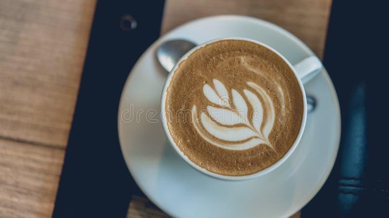 Arte calda del caffè del Latte in tazza bianca fotografie stock libere da diritti