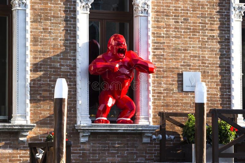 Arte contemporanea: scultura di una scimmia rossa che sta in una finestra immagine stock