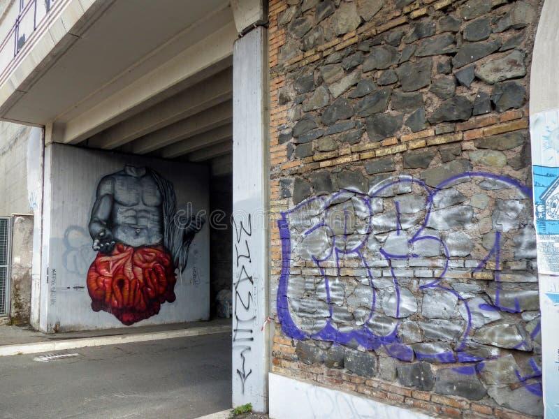 Arte da rua do busto de um homem muscular com intestino vermelho para fora no distrito de Ostiense de Roma em Itália imagem de stock