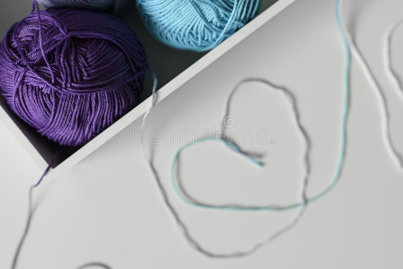 Arte dai fili delle lane tricottare variopinte, progettazione del fondo come simboli dei cuori sulla tavola bianca Fuoco sulle pa fotografie stock libere da diritti