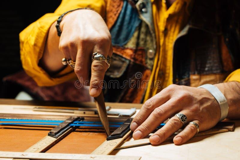 Arte de cuero para la cartera que trabaja con la herramienta en el escritorio de cuero del trabajo del ` s del craftman foto de archivo libre de regalías