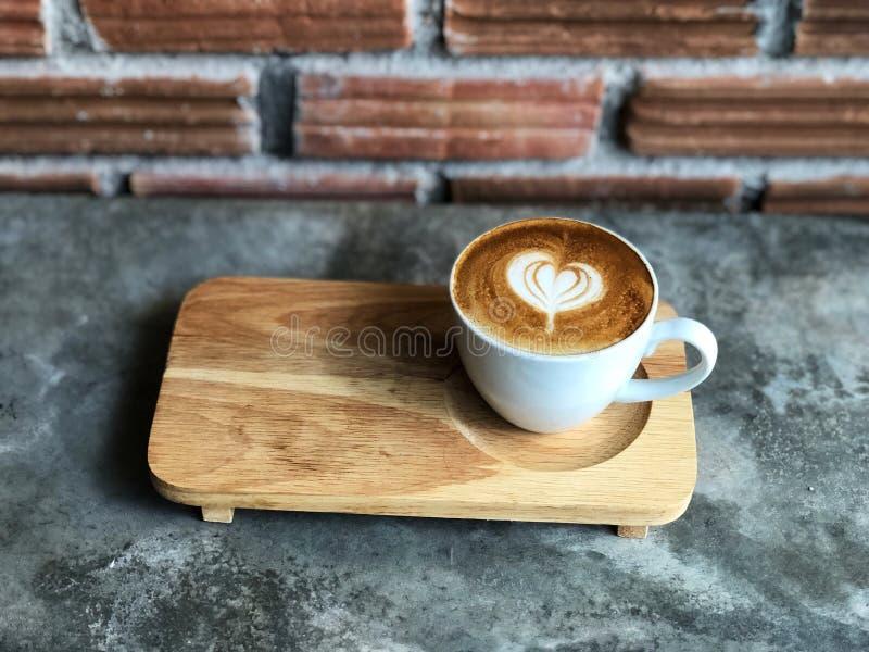 Arte de flautín del latte del amor del corazón en la taza blanca en piso de madera de la bandeja y del cemento con la luz natural imagenes de archivo