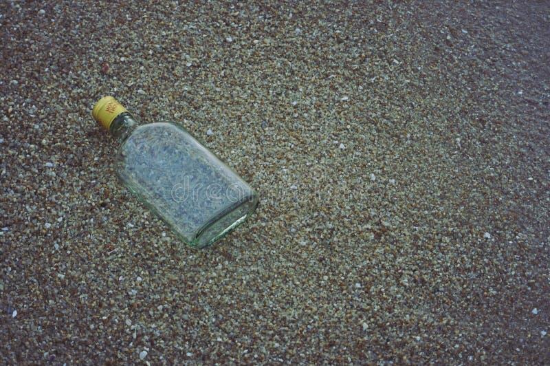 Arte de la botella de cristal en la playa de la arena fotografía de archivo libre de regalías