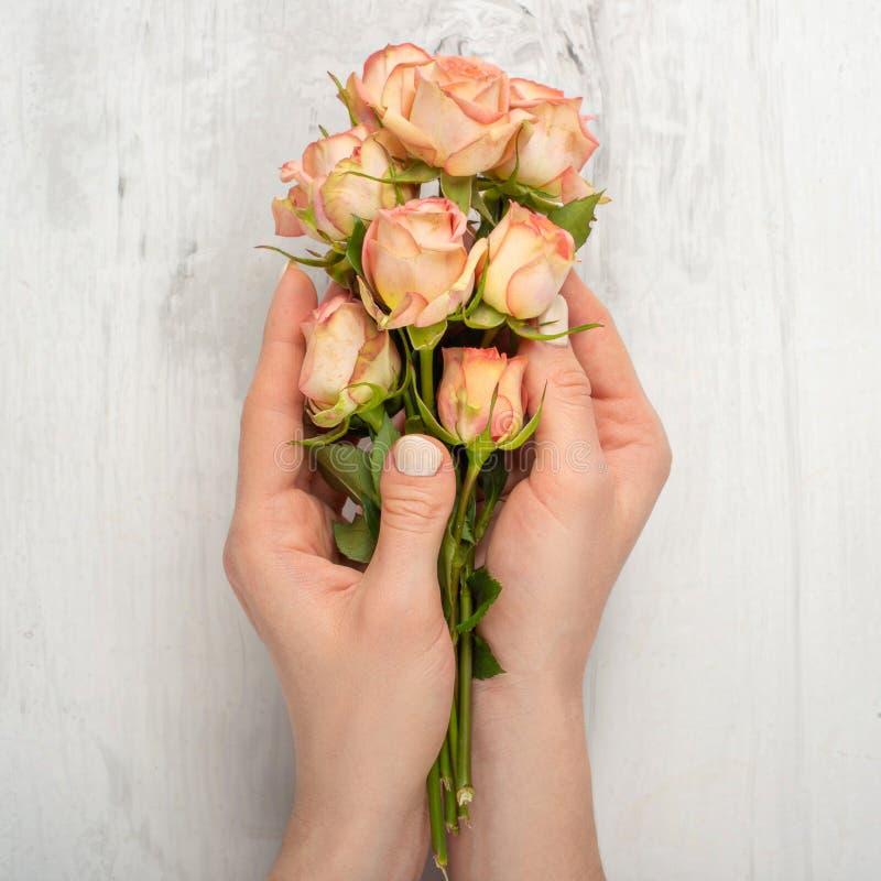 Arte de la moda de la mano de la mujer con las flores en su mano, rosas en su mano con maquillaje que pone en contraste brillante fotos de archivo