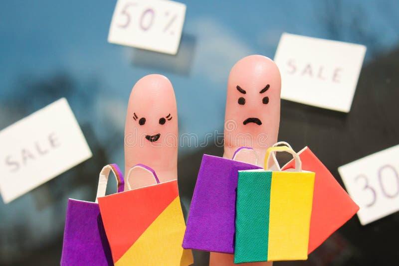 Arte del dito di una coppia con i sacchetti della spesa L'uomo è infelice perché era stanco di acquisto fotografia stock libera da diritti