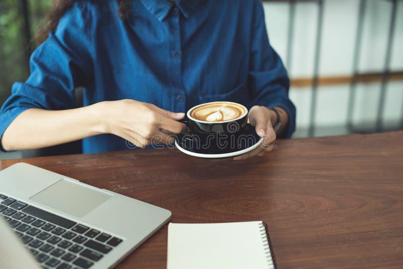Arte del latte del caffè sulla mano della donna in caffetteria immagine stock libera da diritti