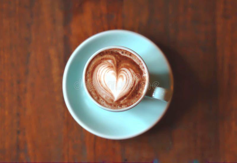 Arte del latte del corazón del chocolate caliente en taza azul en la tabla de madera fotos de archivo