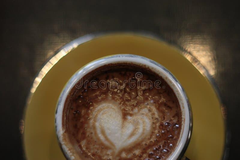 Arte del latte del cuore in una tazza gialla con il piattino fotografia stock