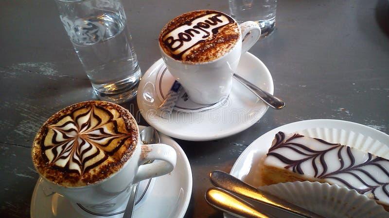 Arte del Latte Due tazze della fine del cappuccino su fotografia stock libera da diritti