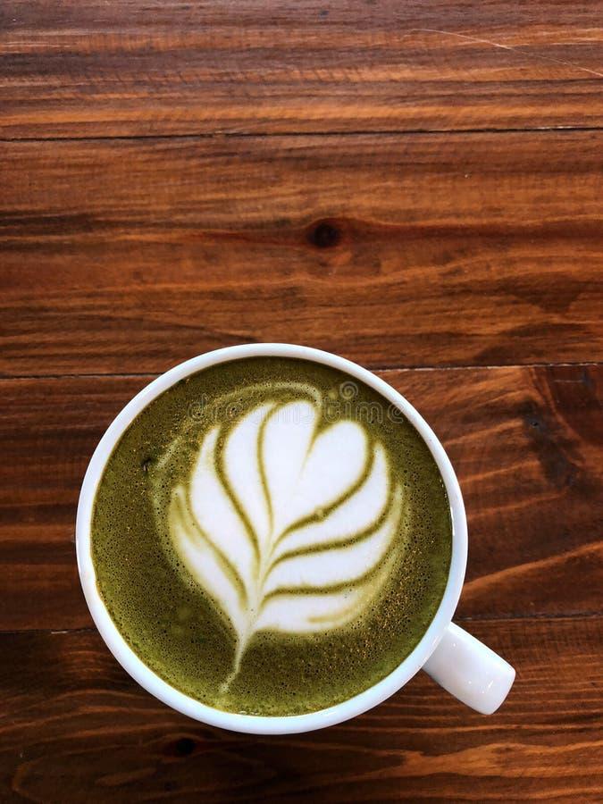 Arte del latte del té verde en la taza blanca en la tabla de madera del vintage fotografía de archivo