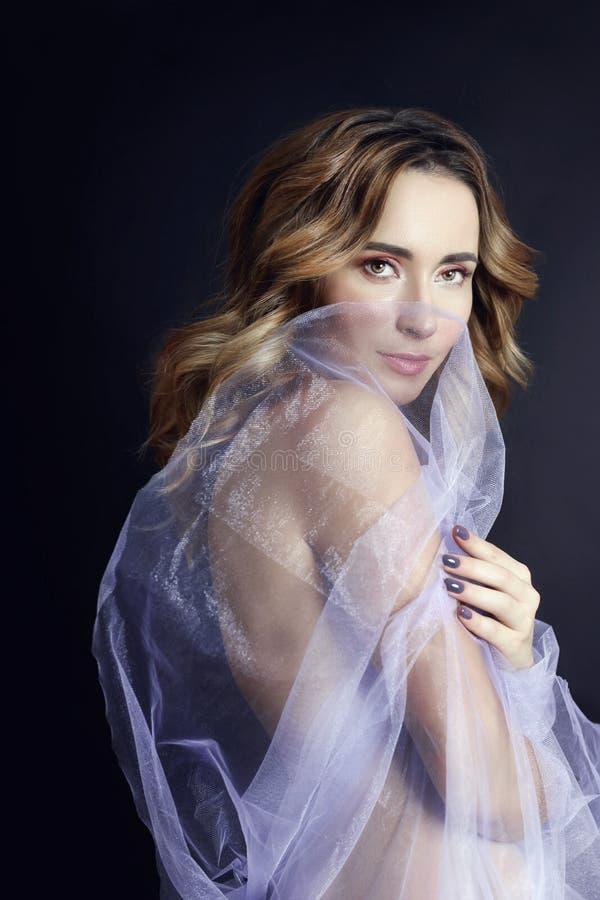 Arte despida da mulher no vestido transparente leve lilás que levanta em um fundo escuro Mulher envolvida na figura magro bonita  foto de stock royalty free
