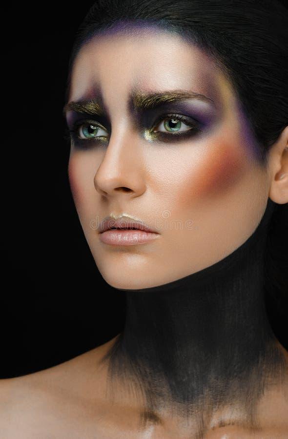 Arte di trucco e bello tema di modello: bella ragazza con un trucco creativo nero-e-porpora e colori dell'oro su un backgroun ner immagini stock