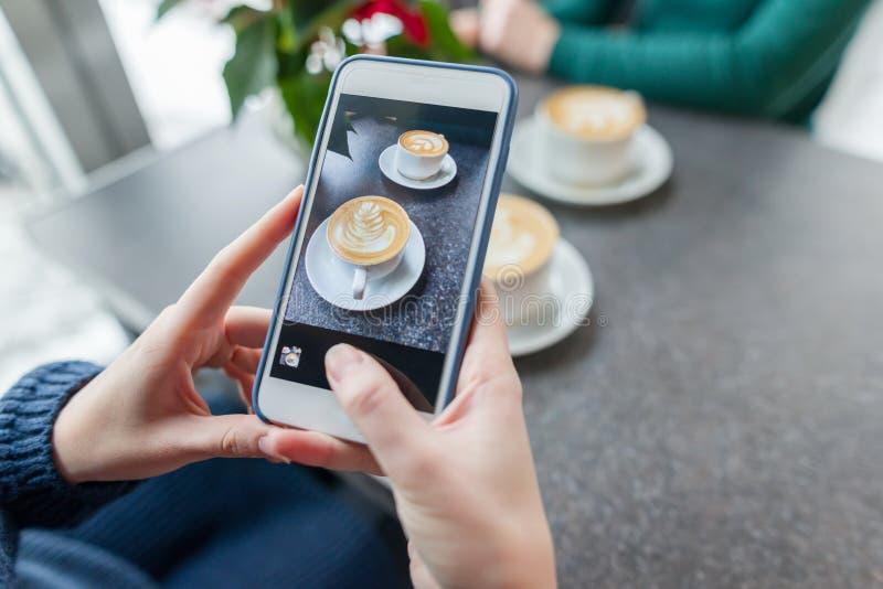 Arte do café, mãos da mulher que tomam a fotos no telefone dois copos com arte do latte, superfície de pedra cinzenta do fundo do fotos de stock