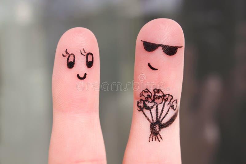 Arte do dedo de pares felizes O homem está dando flores imagem de stock