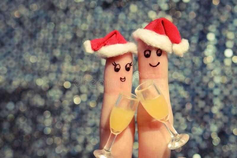 Arte do dedo de um par feliz Acople a fatura do bom elogio nos chapéus do ano novo Dois vidros do champanhe imagem de stock