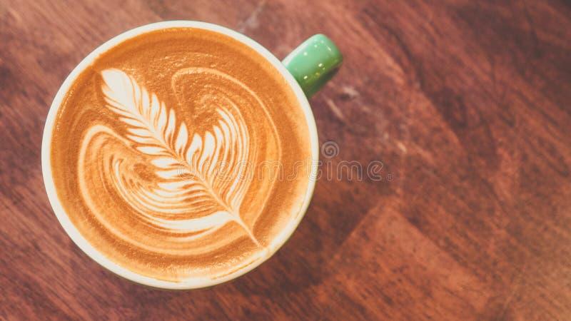 A arte do latte do café na configuração lisa da tabela de madeira, relaxa o tempo, opinião superior da arte do barista do café imagem de stock