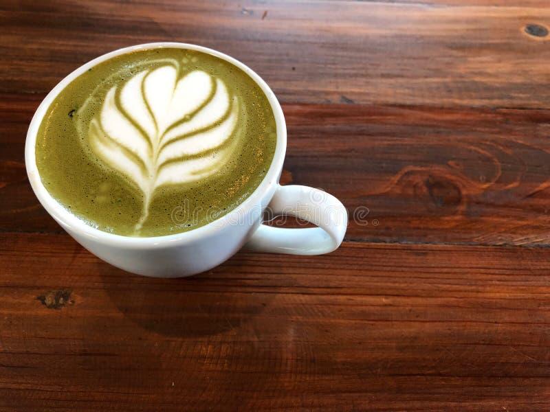 Arte do latte do chá verde no copo branco na tabela de madeira do vintage imagem de stock
