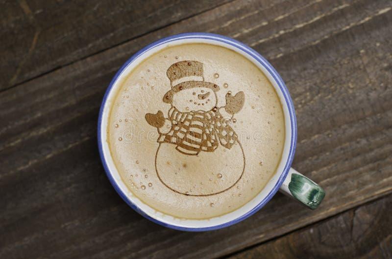 Arte do latte da xícara de café na tabela de madeira Formulário da espuma do boneco de neve foto de stock royalty free