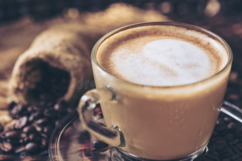 Arte e cappuccino do latte do copo de café com coração-dado forma feito do leite na tabela de madeira com os feijões de café da r imagens de stock