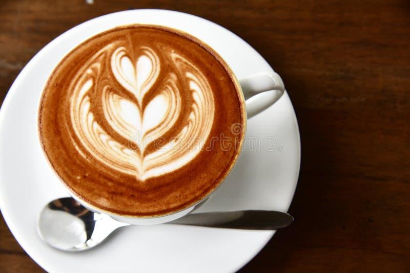 Arte e moca del latte della tazza di caffè del primo piano sulle vecchie sedere di legno marroni fotografia stock