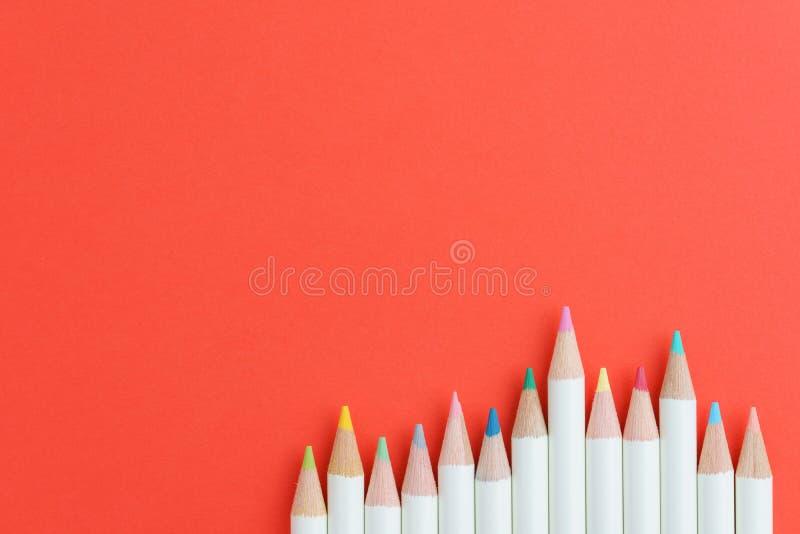 Arte, educación y concepto de la afición que colorea con los lápices del color en fila en fondo rojo con el espacio de la copia fotos de archivo libres de regalías