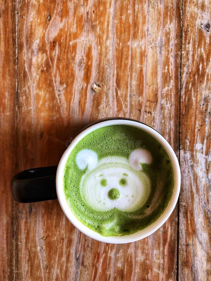Arte lindo del latte de la cara del perro del té verde en la taza blanca fotografía de archivo libre de regalías