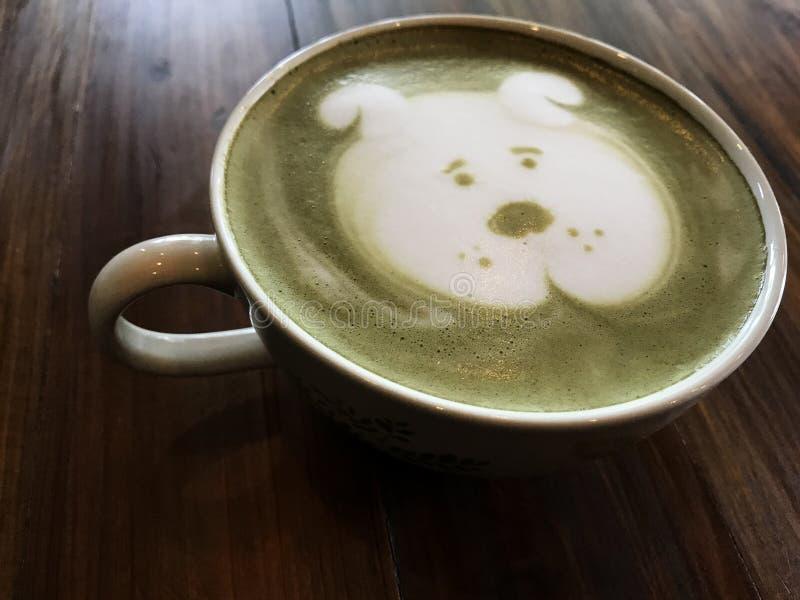 Arte lindo del latte de la cara del perro del té verde en la taza blanca en la tabla de madera imagen de archivo libre de regalías