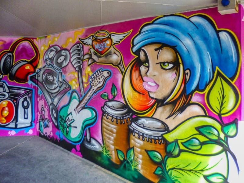 Arte mural da parede dos grafittis de uma menina do músico com cilindro e guitarra do conga fotografia de stock royalty free