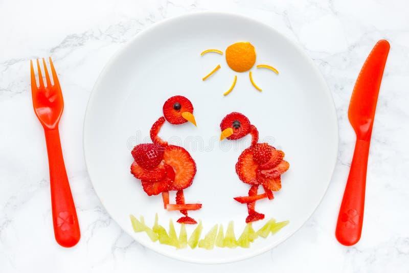 Arte para los niños, flamenco comestible de la comida de la fresa en la placa fotografía de archivo