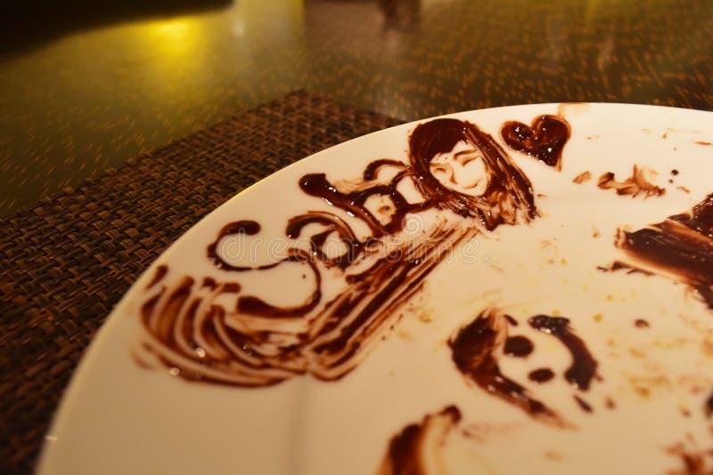 Arte su un piatto - Saba Malaysia del cioccolato con il fronte e un cuore di una ragazza sorridente fotografie stock libere da diritti