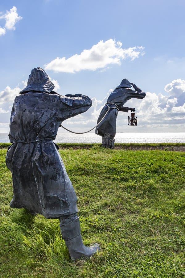 Arte sulla diga delle statue di Ameland dell'isola di due persone in ingranaggio della pioggia che scruta sopra l'acqua fotografia stock libera da diritti