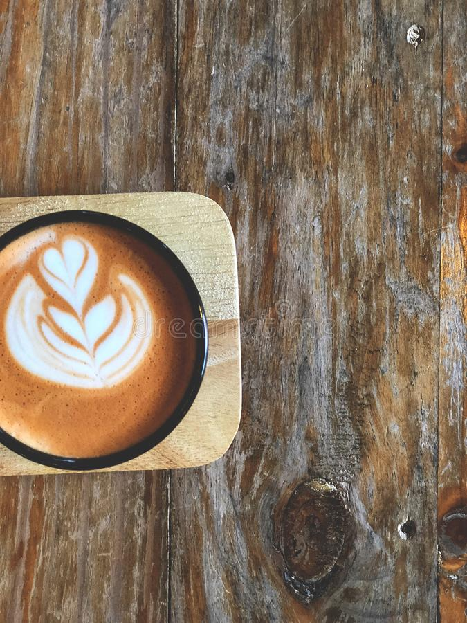 Arte tailandés del latte del té en taza negra en la bandeja de madera con la luz natural Té preferido en Tailandia fotos de archivo