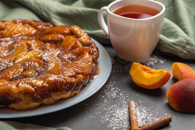 Arte Tatin with peaches, caramel and powdered sugar close-up on a white plate on a dark background with a linen napkin. Next to stock photos