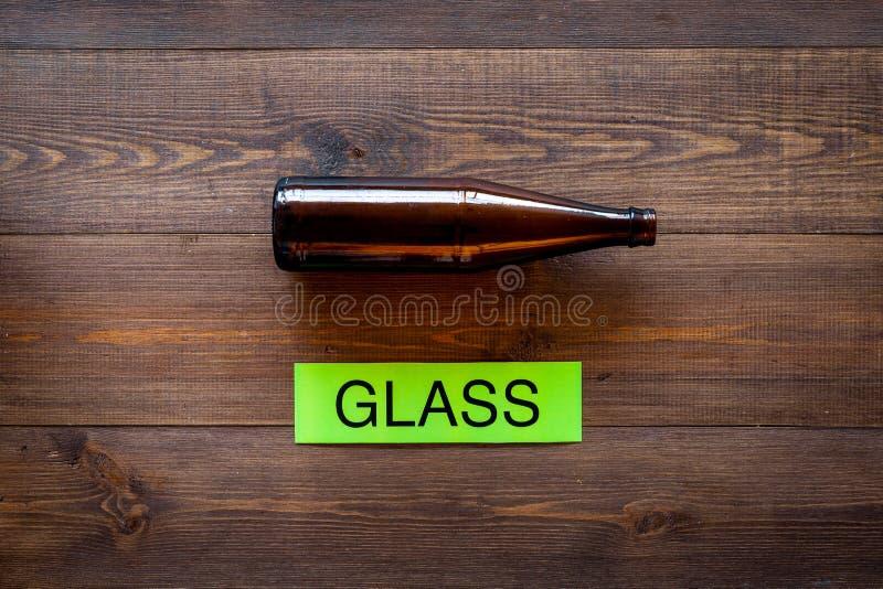 Arten von matherial für reycle und Wiederverwendung Glasflasche nahe druckte Wortglas auf dunklem hölzernem Draufsichtraum des Hi lizenzfreie stockfotografie
