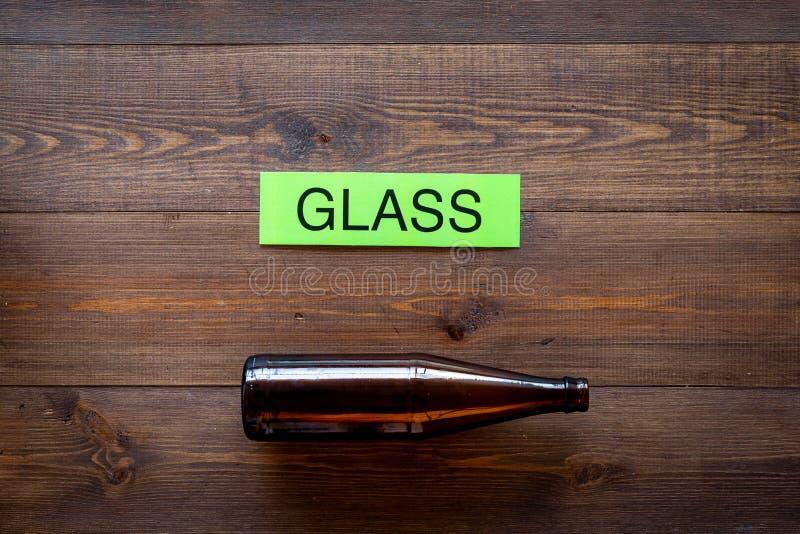 Arten von matherial für reycle und Wiederverwendung Glasflasche nahe druckte Wortglas auf dunklem hölzernem Draufsichtraum des Hi stockfoto