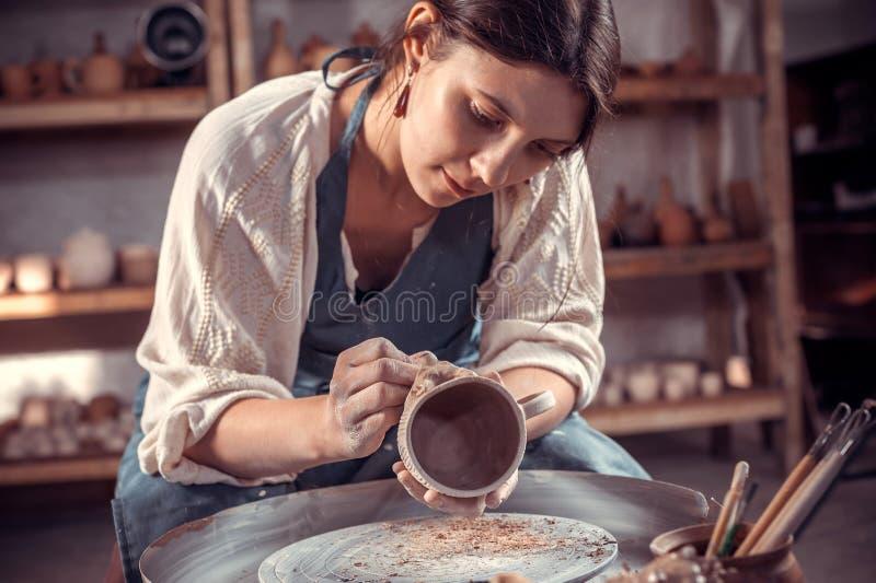 Artesão à moda que faz a cerâmica, escultor da argila molhada na roda Fabrica??o do of?cio foto de stock