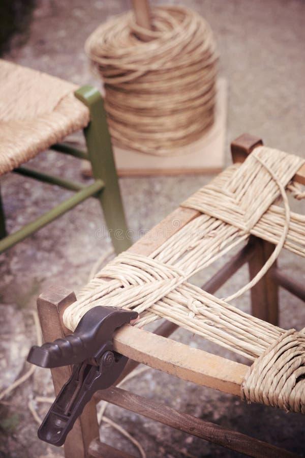 Artesão antigo do ofício das continuações às cadeiras da palha fotografia de stock royalty free