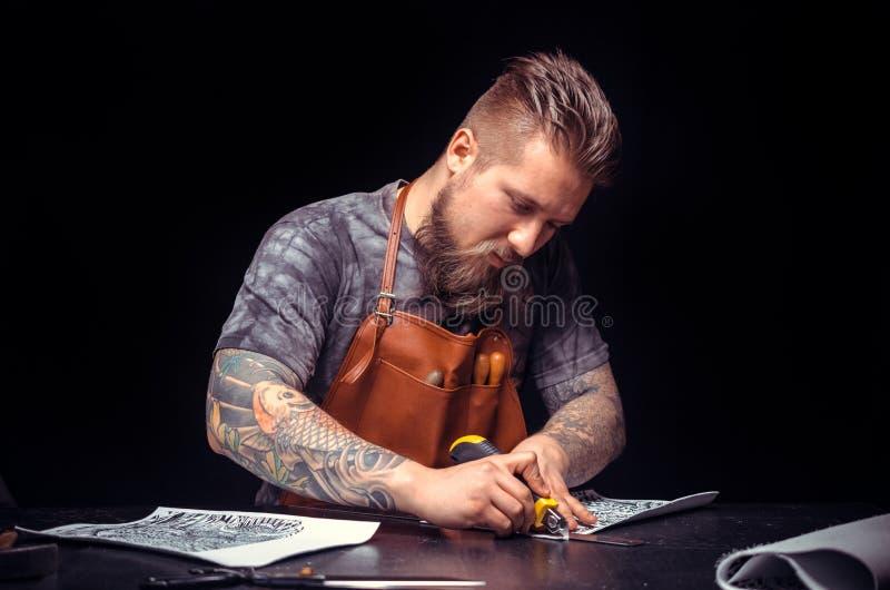 Artes?o de couro que processa um workpiece de couro em sua loja do curtidor foto de stock