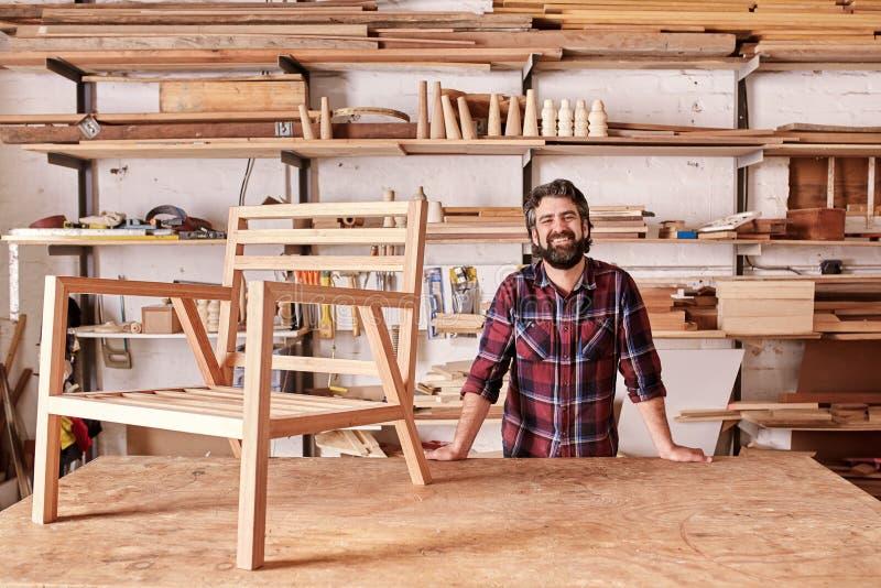 Artesão de sorriso em seu estúdio da carpintaria com quadro de madeira da cadeira foto de stock royalty free
