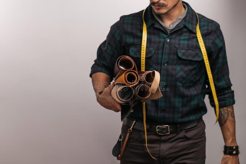 Artesão do couro no chapéu negro criativo que levanta com os bens de couro no estúdio fotografia de stock
