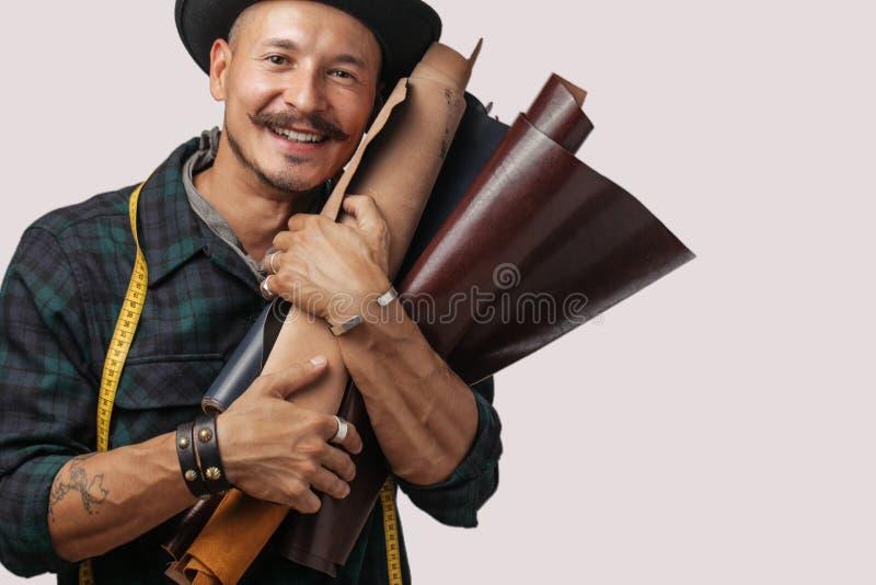 Artesão do couro no chapéu negro criativo que levanta com os bens de couro no estúdio imagem de stock