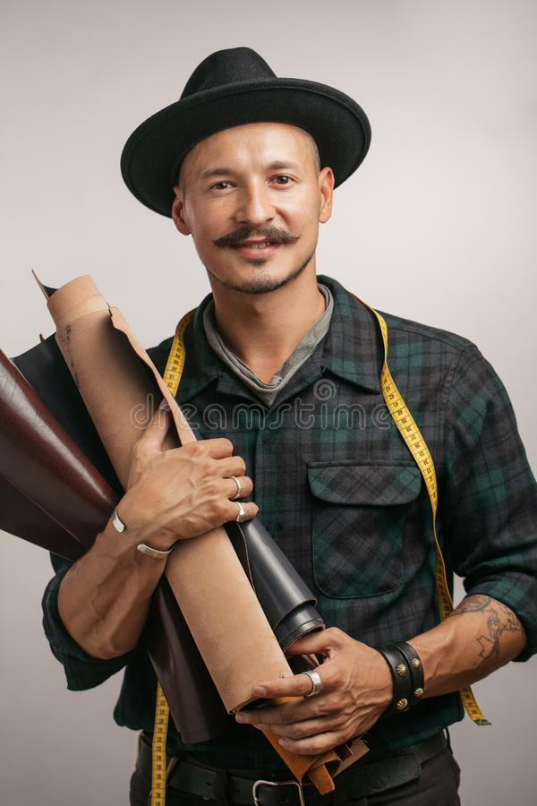 Artesão do couro no chapéu negro criativo que levanta com os bens de couro no estúdio imagem de stock royalty free