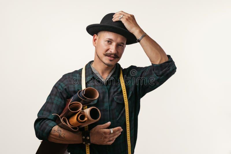 Artesão do couro no chapéu negro criativo que levanta com os bens de couro no estúdio foto de stock