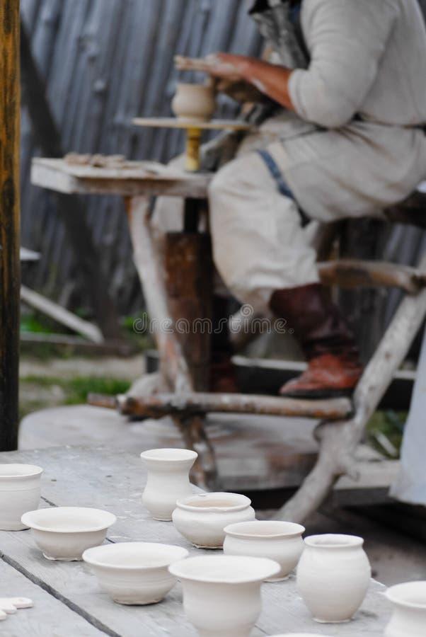 Artesão que faz o vaso da argila molhada fresca na roda da cerâmica fotografia de stock royalty free